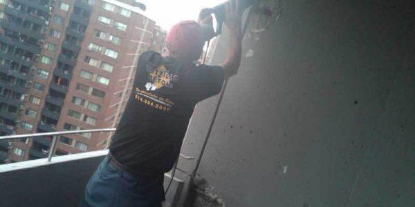 Employé qui effectue une réparation d'un balcon en béton